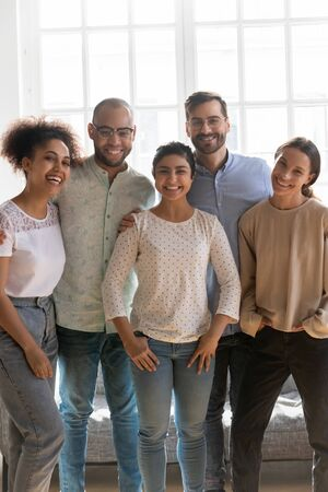 Vertical view five cheerful attractive multi-ethnic best friends standing indoors pose smiling looking at camera feels happy, representatives of millennial generation, group of students people concept Banco de Imagens