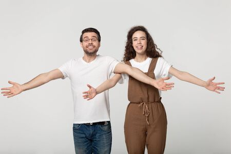 Excited smiling millennial couple looking at camera making big hugs gesture, welcoming clients or happy to see friends, nice to meet you free hugs concept, isolated on grey white studio background.