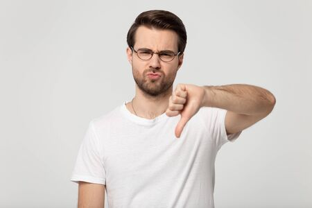Head shot close up portrait millennial guy in eyeglasses showing thumbs down gesture. Satisfied female customer disliking service or product, refusing sign, isolated on grey white studio background.