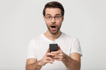 Amazed happy millennial guy holding mobile phone in hands, received unexpected win news, looking at camera head shot portrait. Excited young man got free app download, isolated on grey background.