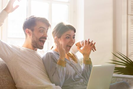 Excited couple scream raising hands look at laptop amazed by hitting jackpot, winning online lottery, overjoyed man and woman feel euphoric stare at computer receive unexpected unbelievable news