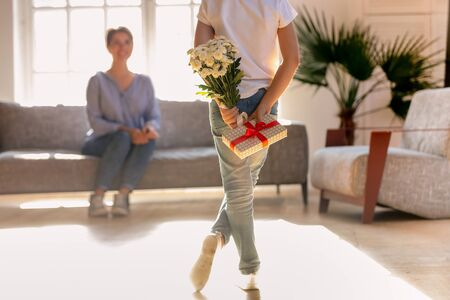 Loving child hold flowers and gift box behind back greeting smiling young mom with birthday, caring kid hide bouquet and present making surprise for happy parent, congratulating mother at home