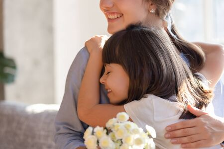 Close up of loving little daughter hug young happy mom presenting flowers congratulating with birthday or special occasion, caring cute preschooler girl embrace mother greeting with bouquet