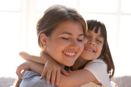 Close up of loving young mom and little daughter hug cuddle showing care and affection, cute small girl child embrace happy mother or nanny, enjoy tender sweet moment at home together Stockfoto