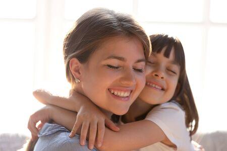 Nahaufnahme einer liebevollen jungen Mutter und einer kleinen Tochter, die sich umarmen, die Sorgfalt und Zuneigung zeigen, süße kleine Mädchen umarmen glückliche Mutter oder Kindermädchen, genießen einen zarten süßen Moment zu Hause zusammen Standard-Bild