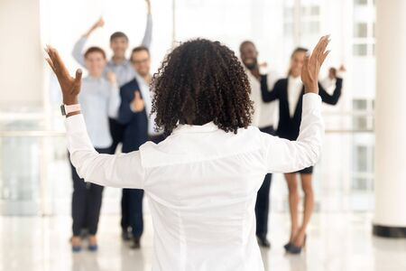 Back view of african American team business leader raise hands motivate excited diverse employees, confident successful black businesswoman make speech unify supportive employees. Leadership concept