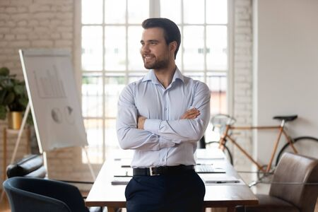 Portrait of satisfied millennial caucasian businessman posing with arms crossed standing inside of modern office boardroom looking away dreaming planning future successful projects, leadership concept Foto de archivo