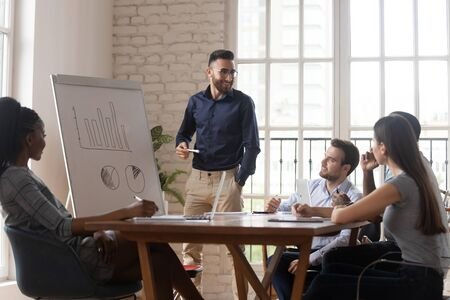Middle eastern ethnicity young business coach give knowledge to diverse staff standing near flip chart diagram forecast results of sales growth shown on it, concept of corporate training and mentoring Foto de archivo