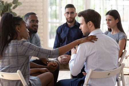 African psychologist supporting male rehab session participant put hand on newcomer shoulder talks encouraging words, medical detox center, psychological help activity struggle with addictions concept