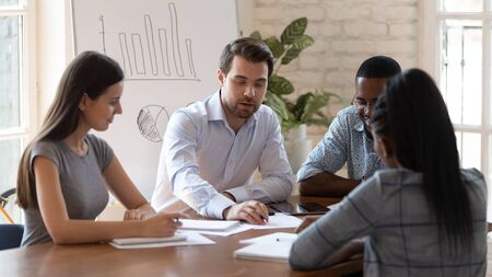 Les stagiaires multinationaux acquièrent les connaissances d'un coach qualifié en affaires participent à un séminaire d'entreprise, le personnel de l'entreprise écoute le chef d'équipe faire de la paperasse discuter des tâches ensemble, du travail d'équipe et du concept de mentorat