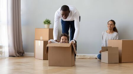 Happy African American family moving, having fun in new apartment, smiling father playing with little son, preschool child riding in cardboard box, family unpacking belongings, celebrating relocation