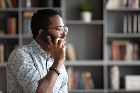 Head shot side view pleasant handsome biracial man in glasses talking on phone, ordering taxi or food delivery indoors. Smiling young african american businessman holding call with partners clients. Stock fotó