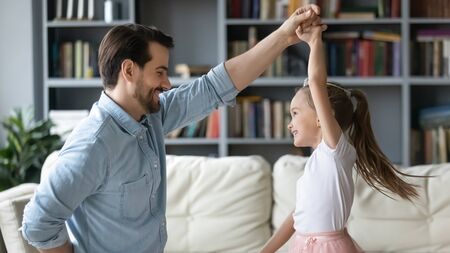 Happy young father dancing with excited little preschooler daughter in princess dress in living room, smiling overjoyed dad have fun play with small girl child, enjoy family weekend together 스톡 콘텐츠