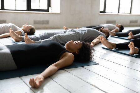 Diverse people resting after work out lying on carpets performing Shavasana or Corpse Dead position focus on African female, final pose of yoga class deep restoration, body and mind relaxation concept Stock Photo