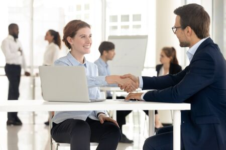 Smiling attractive woman candidate shaking hands with businessman. Happy female job seeker with boss employer man at job interview, successful employee business negotiation with partner.