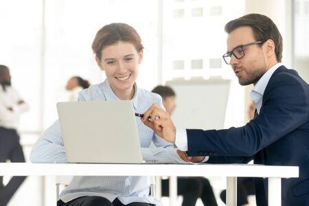 Lächelnder Mentortrainergeschäftsmann, der Geschäftsfrau beim persönlichen Treffen ausbildet. Fun Man Mitarbeiter berät weibliche Kunden, männliche Kollegen zeigen am Laptop und präsentieren der weiblichen Führungskraft ein neues Projekt.