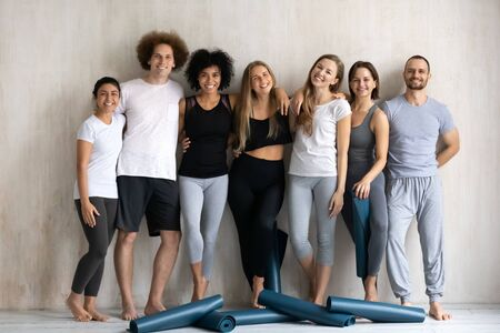Before group training multi-ethnic millennial slim people standing near wall background hugging smiling posing look at camera, girls guys wearing comfy cool sportswear photo shooting after work out