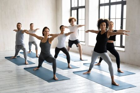 Multinational millennial girls and guys standing barefoot on mats performing Warrior II or Virabhadrasana position. Session led by mixed-race woman trainer showing exercise to people during yoga class