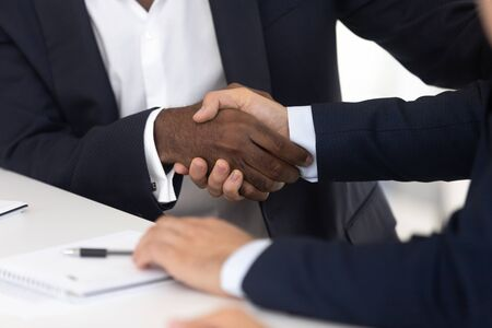 Close up of male handshake after effective negotiation. African american and white men shaking hands making agreement, success business conversation with partner, man racial equality in relationship.