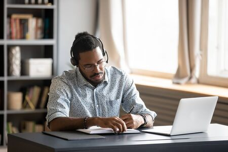 Concentrated millennial african american guy wearing earphones, listening to favorite music while planning workday. Focused young biracial businessman watching educational lecture. writing down notes.