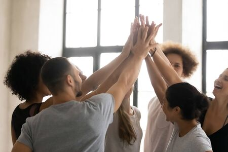 Group of happy multi-ethnic sportive people stacked palms together celebrating sport victory at competition, teambuilding activity in training studio, mates giving high five show unity support concept