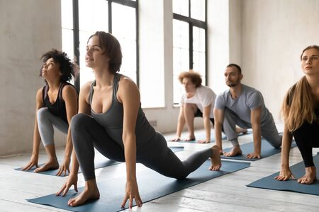 Yoga class led by woman trainer shows to multi-ethnic group of people Low Lunge Forward Ashva Sanchalanasana pose. Exercise help strengthen, stretch body, improve balance, healthy life habits concept