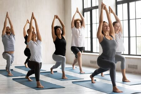 Group of active multiracial young people performing Warrior I Virabhadrasana yoga position practising exercise during session, working out in sport club, asana builds focus power stability and balance