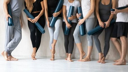 Group of young slim sporty girls and guys wearing comfy stylish sportswear holding personal carpets leaned on wall background waiting for yoga class. Concept of hobby, healthy lifestyle and wellness