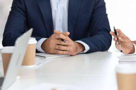 Clouse up businessman hands at work meeting with employee. Boss discussing corporate business plan at group office, worker man sitting at conference table at company briefing
