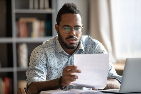 Focused serious millennial african american businessman in glasses reading bank loan payment notification paper, sitting at table with computer. Concentrated businessman analyzing research report. Stock fotó