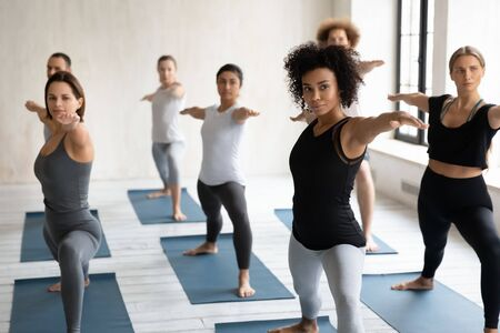 Group of people standing barefoot on mats performing Warrior 2 two asana or Virabhadrasana II training led by African instructor, physical mental emotional balance, lifestyle, healthy habits concept Banque d'images