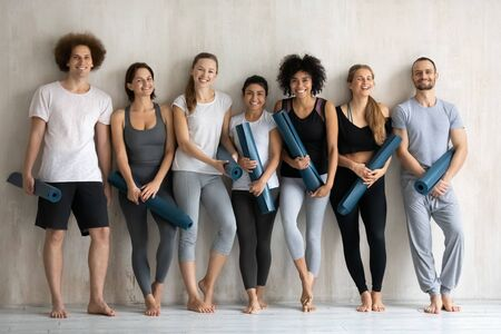 Group of sportive diverse people wearing activewear holding personal mats standing barefoot on warm floor waiting for yoga class leaned on wall smiling looking posing for camera, keeping fit concept