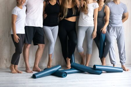 Rolled mats lie at the barefoot feet of sportive slim people in sportswear standing in row embracing ready for class at sport club studio after work out rest, group training, active lifestyle concept
