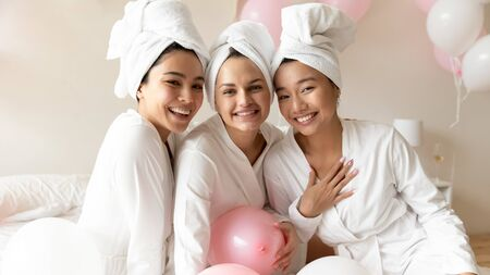 Head shot portrait happy diverse young women wearing bathrobes and towel on heads celebrating wedding or birthday in spa, sitting on bed together, looking at camera, having fun at hen party Standard-Bild