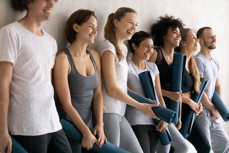 Sportive diverse people wearing comfy stylish sportswear holding yoga mats leaned on wall ready for training at gym. Wellness, sport club studio staff portrait, seminar, team building activity concept
