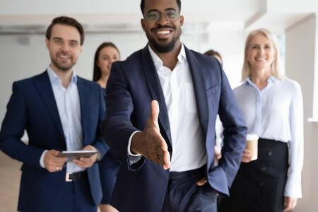 Group portrait of smiling multiracial businesspeople greeting newcomer to successful team, happy African American businessman stretch hand get acquainted with job applicant, recruitment concept Stockfoto