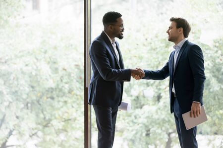 Happy multiracial male business partners shake hands get acquainted greeting at office meeting, smiling diverse businessmen handshake closing deal after successful negotiation, partnership concept