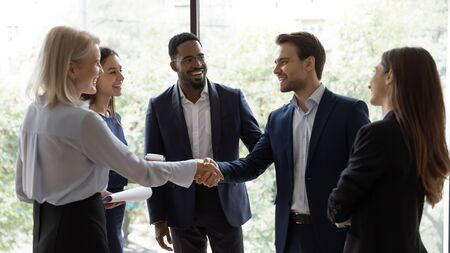 Smiling diverse businesspeople shake hands greeting getting acquainted at office meeting, happy colleagues employees handshake closing deal or making agreement after successful negotiations