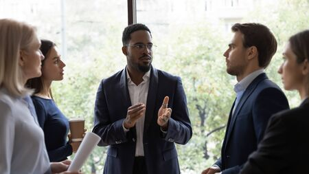 Concentrated diverse businesspeople stand talk discuss business ideas project together, focused multiracial colleagues employees brainstorm, cooperating in office, collaboration, teamwork concept