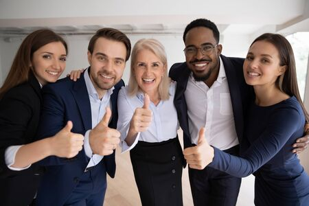 Group portrait of smiling multiracial colleagues posing in office show thumbs up recommend good service, happy diverse businesspeople give recommendation of company, acknowledgment concept