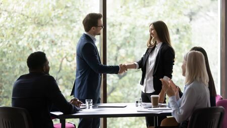 Smiling young Caucasian businessman shake hand greeting with promotion excited female employee, happy male boss or director handshake get acquainted congratulate woman colleague at meeting