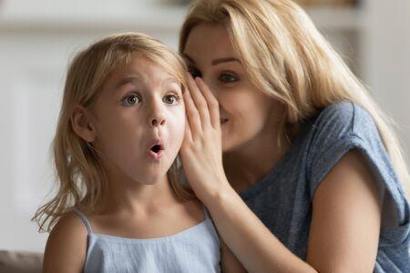 Une jeune mère chuchote dans l'oreille d'une petite fille mignonne surprise qui raconte un secret, une maman millénaire ou une nounou jouent avec une petite fillette d'âge préscolaire, partagent un moment intime à la maison, bavardent ou discutent ensemble