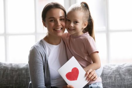 Smiling attractive young mother holding greetings card, cuddling little daughter, looking at camera. Portrait of positive two generations family sitting on sofa, celebrating birthday or special event.