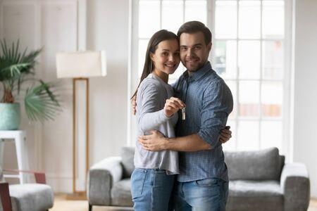 Happy affectionate young family couple embracing in modern living room, showing keys to camera. Excited loving spouses husband wife homeowners celebrating moving in new apartment, real estate concept.