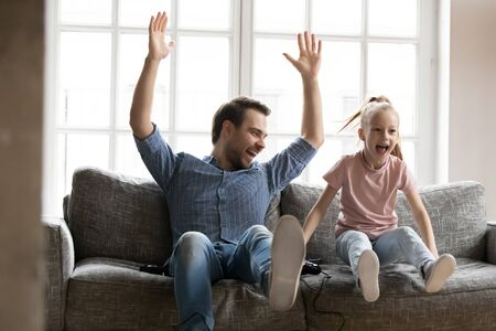 Excited young father raising hands, celebrating video game win with screaming overjoyed little child daughter. Playful small girl enjoying playing games with happy laughing dad, weekend hobby time.