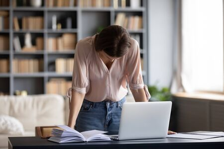 Stressed worried freelance worker standing at table with computer, feeling tired of work. Overwhelmed frustrated young woman stand with bowed head, failed with test results, get message with bad news. Stock Photo