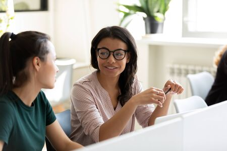Diverse millennial female employees talk discuss business ideas collaborating using computer in office, multiracial woman coworkers speak brainstorm consider project or plan cooperating at workplace