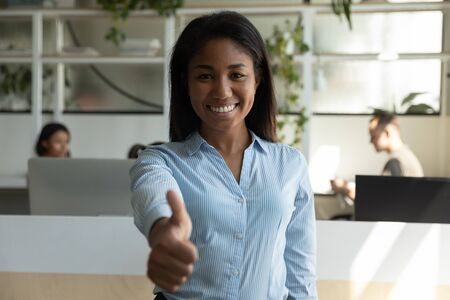 Portrait of smiling African American young female employee pose in modern office show thumbs up give recommendation, happy biracial millennial woman worker or client recommend good service