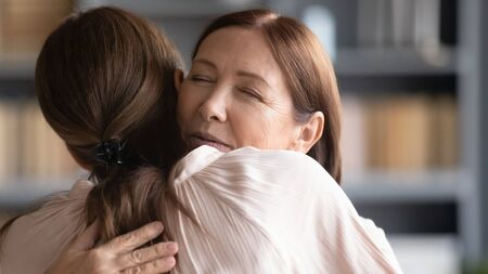 Loving affectionate middle aged mature woman embracing young daughter after reunion. Emotional pleasant senior older mother cuddling grownup child, glad to see welcoming at home, head shot close up.