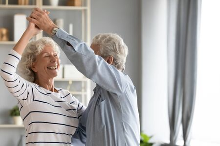 Overjoyed elderly 60s couple spouse dance swirl in living room together, happy smiling mature retired husband and wife have fun engaged in funny activity, feel optimistic active enjoy weekend together